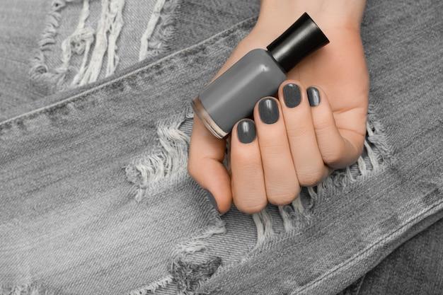 Mão feminina com design de unhas cinza segurando verniz de metal na superfície do jeans.