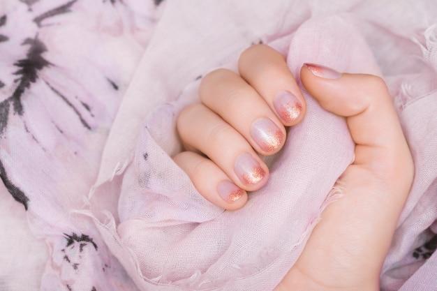 Mão feminina com design de unhas de glitter rosa.
