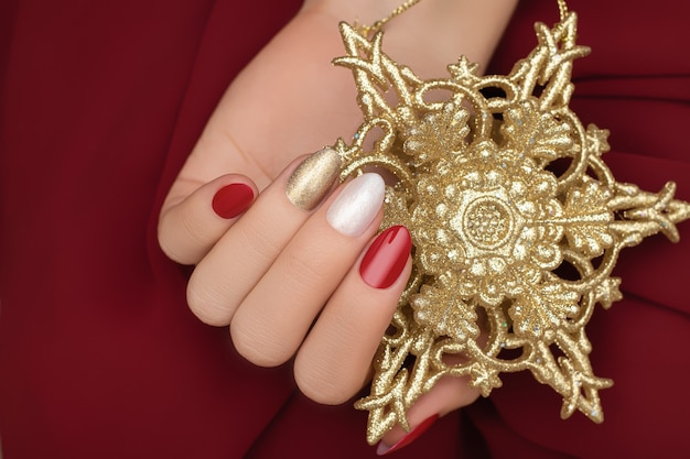 Mão feminina com design de unhas de natal segurando uma estrela dourada de ano novo.