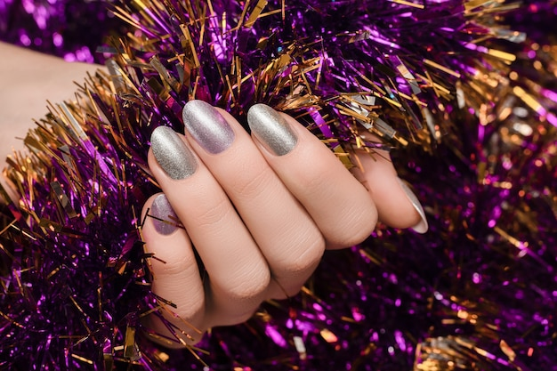 Mão feminina com design de unhas de natal.