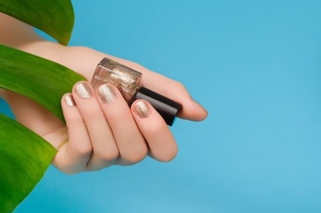 Mão feminina com design de unhas de ouro.