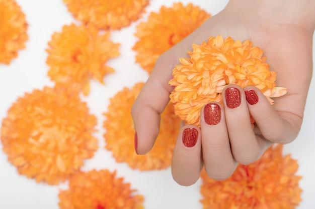 Mão feminina com design de unhas glitter vermelho segurando flor de orquídea laranja.