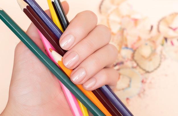 Mão feminina com design de unhas nuas segurando o lápis