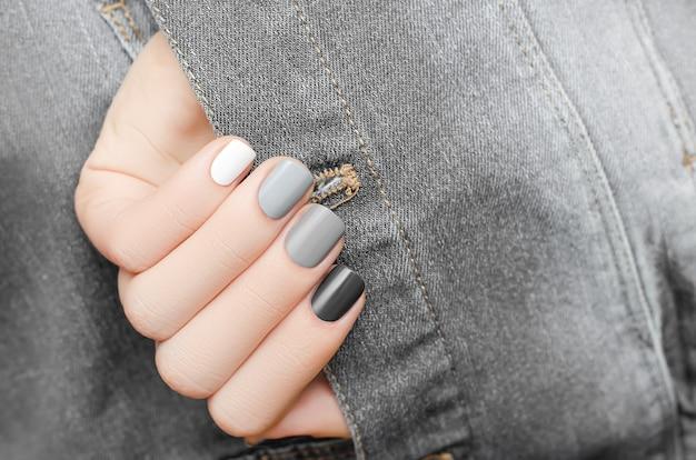 Mão feminina com design de unhas prateado na superfície de tecido jeans irregular cinza.