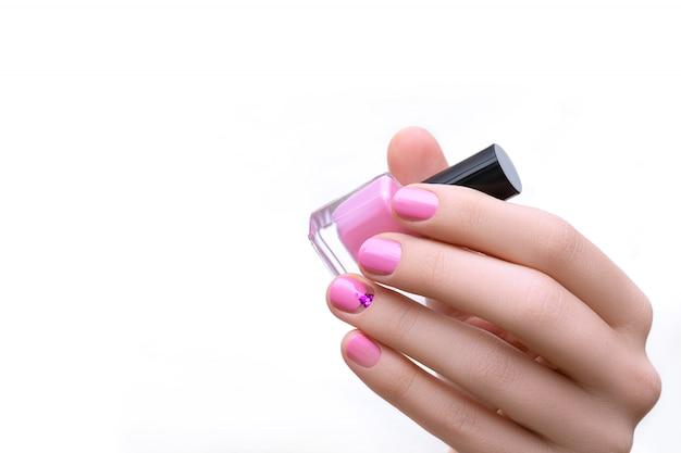 Mão feminina com design de unhas rosa segurando a garrafa de esmalte roxo.