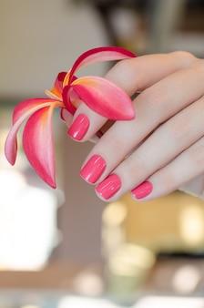 Mão feminina com design de unhas rosa segurando flor rosa.