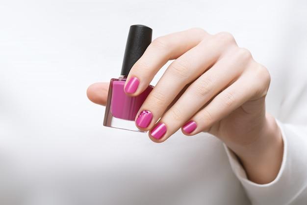 Mão feminina com design de unhas rosa segurando o frasco de esmalte