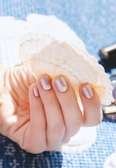 Mão feminina com design de unhas roxas luz com decoração de conchas do mar.