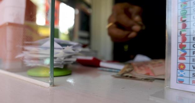 Mão feminina com dinheiro na janela do departamento de dinheiro