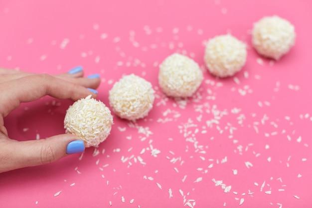 Mão feminina com doces cobertos por coco ralado. bolas de coco em fundo rosa