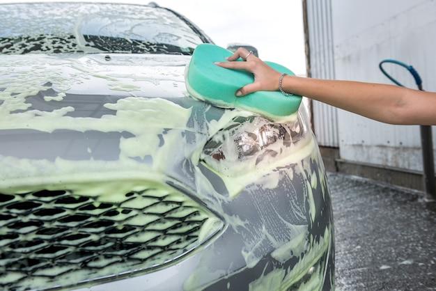 Mão feminina com esponja de espuma de sabão, lavando o carro em um lava-rápido self-service ao ar livre