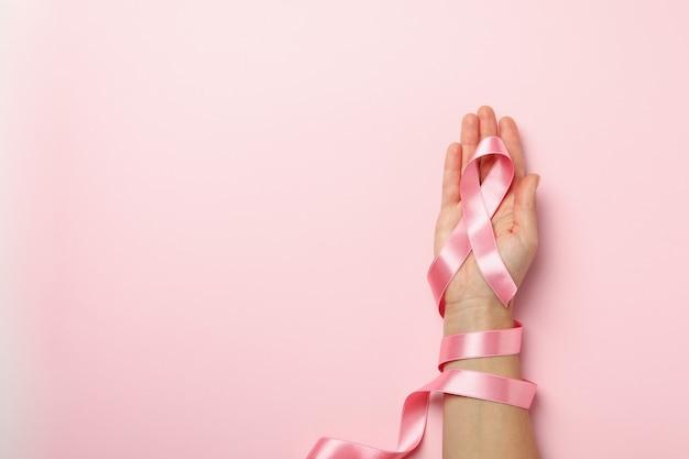 Mão feminina com fita rosa da consciência
