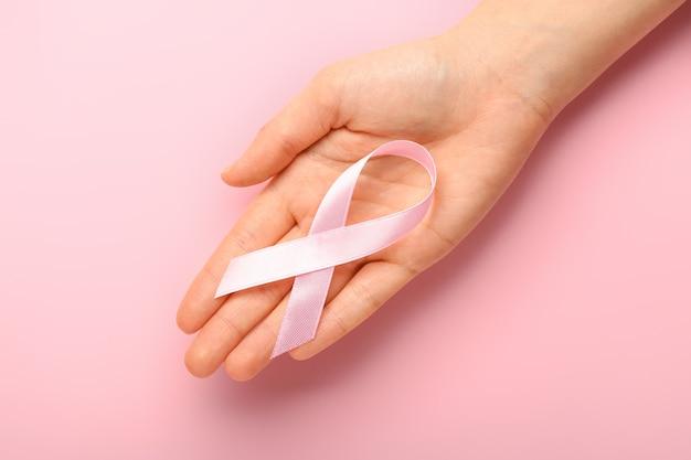 Mão feminina com fita rosa na cor de fundo. conceito de conscientização do câncer