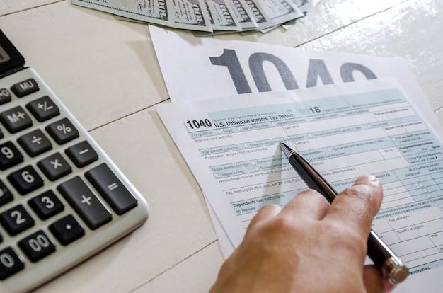 Mão feminina com formulários de imposto de caneta 1040 e dólares em fundo de madeira