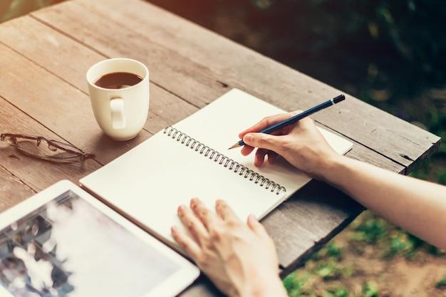 Mão feminina com lapis escrevendo no caderno. mulher com lápis escrevendo no caderno na cafeteria.