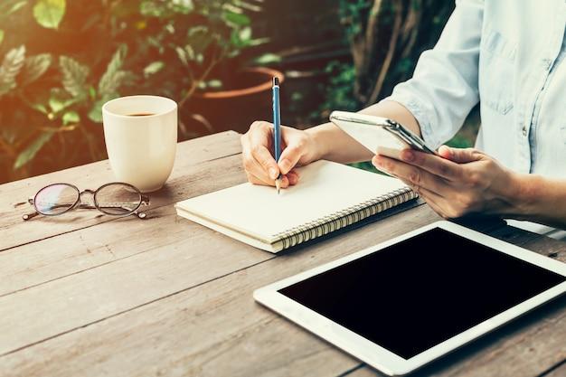 Mão feminina com lapis escrevendo no caderno. mulher segurando o telefone com lápis escrevendo no caderno na cafeteria.