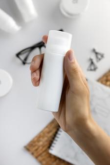Mão feminina com loção creme hidratante cosmética com espaço de cópia na mesa branca