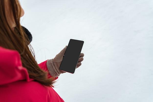 Mão feminina com luva de inverno e casaco de inverno vermelho segurando um telefone inteligente com tela em branco para espaço de cópia