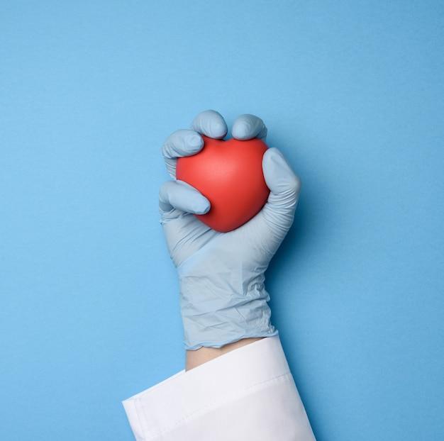 Mão feminina com luvas de látex azuis segurando um coração vermelho, conceito de doação, vista superior