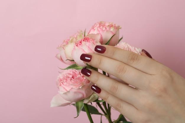 Mão feminina com manicure e rosas em rosa