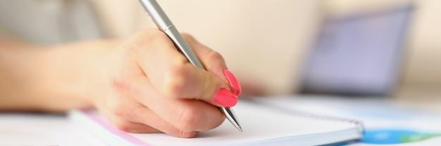 Mão feminina com manicure faz anotações com uma caneta prateada a mulher escreve a distância