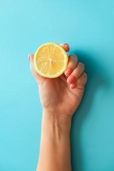 Mão feminina com manicure laranja brilhante com limão amarelo sobre fundo azul