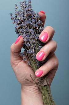 Mão feminina com manicure rosa brilhante segurando um buquê de lavanda