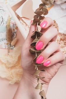 Mão feminina com manicure rosa brilhante segurando um galho de eucalipto dourado