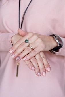 Mão feminina com manicure rosa pastel recém-feita