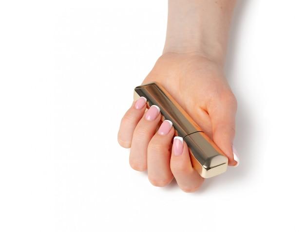 Mão feminina com manicure segurando o tubo de rímel de ouro