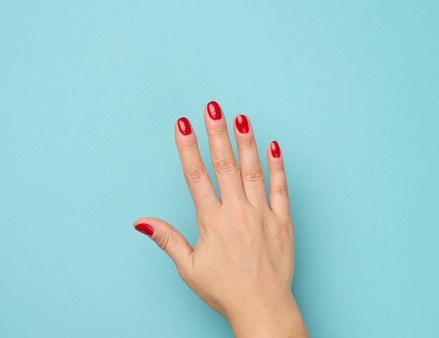 Mão feminina com manicure vermelha levantada sobre um fundo azul