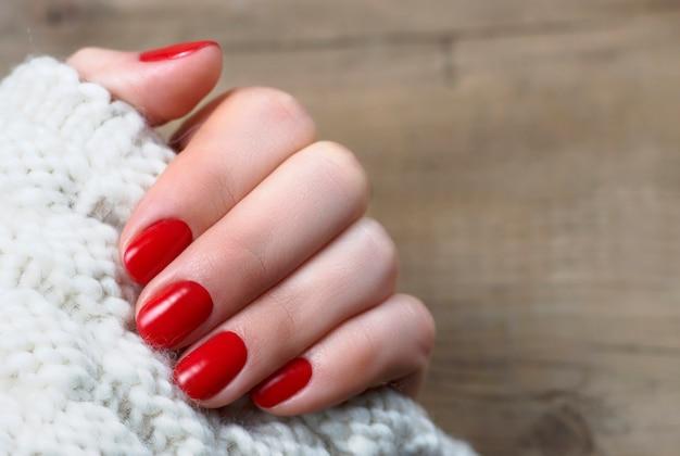 Mão feminina com manicure vermelho sobre um fundo branco de malha com espaço de cópia, vista superior