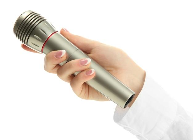 Mão feminina com microfone isolado no branco