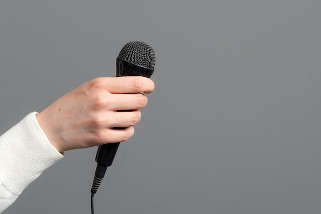 Mão feminina com microfone na superfície cinza, close-up