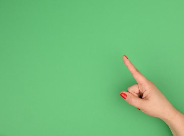 Mão feminina com o dedo indicador levantado em fundo verde