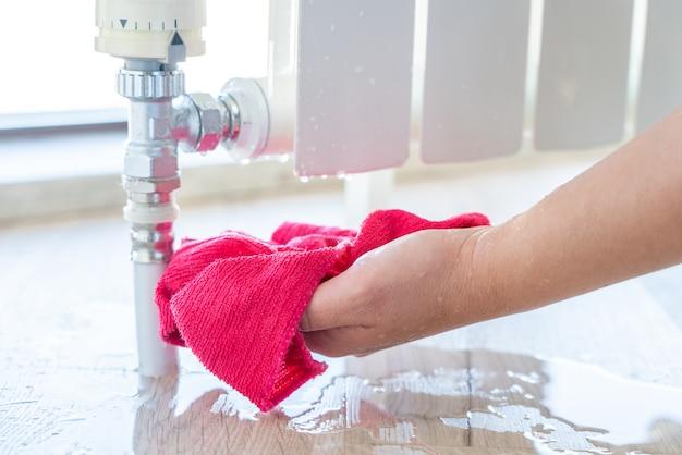 Mão feminina com pano de limpeza de água de vazamento de radiador de aquecimento