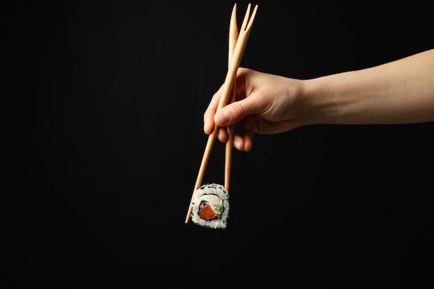 Mão feminina com pauzinhos segurar o rolo de sushi na superfície preta. comida japonesa