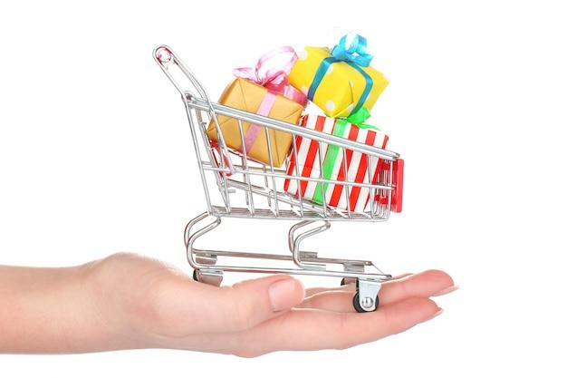 Mão feminina com pequeno carrinho de compras cheio de presentes, isolado no branco
