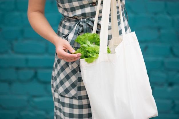 Mão feminina com saco de algodão eco. zero conceito de resíduos