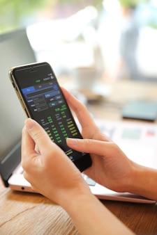 Mão feminina com smartphone negociando ações on-line em uma cafeteria