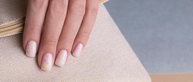 Mão feminina com um belo close-up de manicure branco. bandeira
