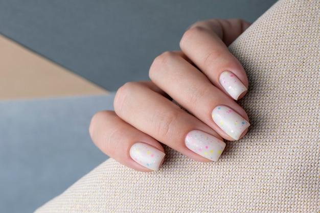 Mão feminina com um belo close-up de manicure branco.