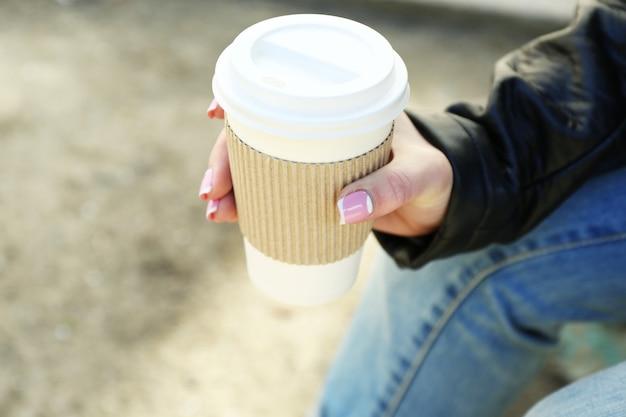 Mão feminina com um copo de papel de café ao ar livre, closeup