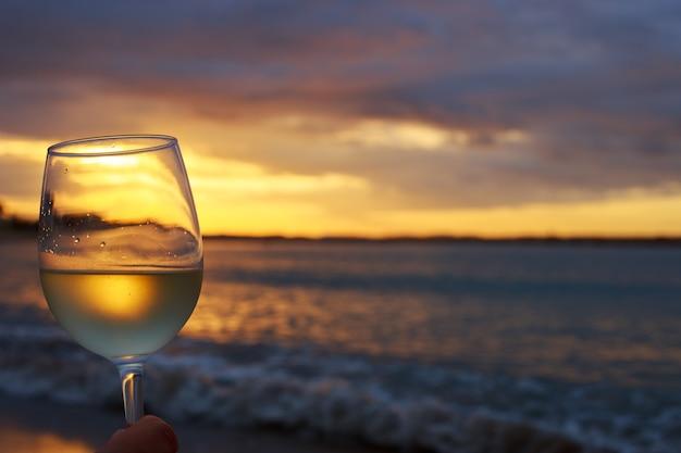 Mão feminina com um copo de vinho branco com um belo pôr do sol. conceito de férias de viagens.