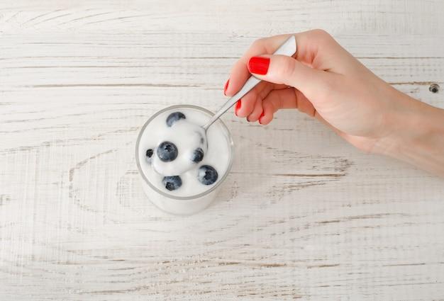 Mão feminina com um iogurte de colher com mirtilos na mesa de madeira branca, vista superior