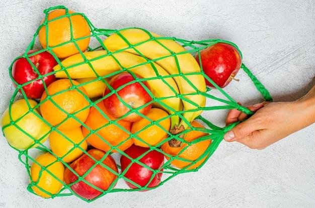 Mão feminina com um saco de corda com frutas mistas: bananas, limões, maçãs, laranjas.