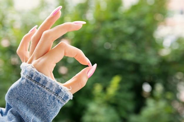 Mão feminina com uma bela manicure rosa mostra ok.