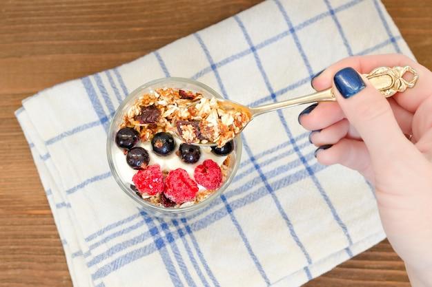 Mão feminina com uma colher de granola, frutas vermelhas e iogurte