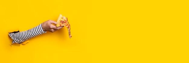 Mão feminina com uma fatia de pizza quente fresca em um rasgado