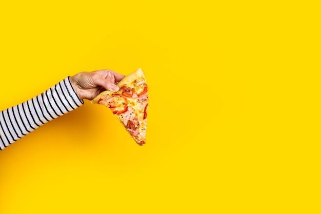 Mão feminina com uma fatia de pizza quente fresca